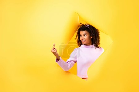 happy african american woman showing middle finger through hole in ripped paper on yellow background