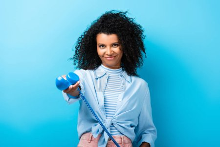 pleased african american woman holding retro telephone on blue