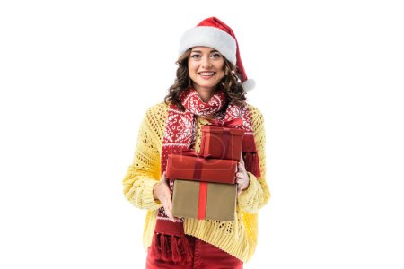 Photo for Joyful young woman in santa hat and scarf holding gifts isolated on white - Royalty Free Image