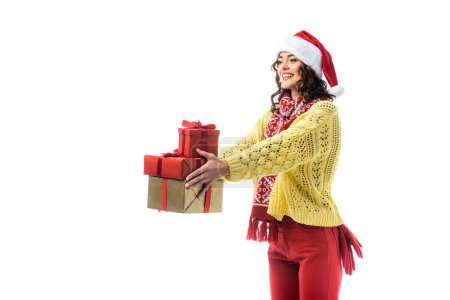 joyful young woman in santa hat, scarf and knitted sweater holding gifts isolated on white