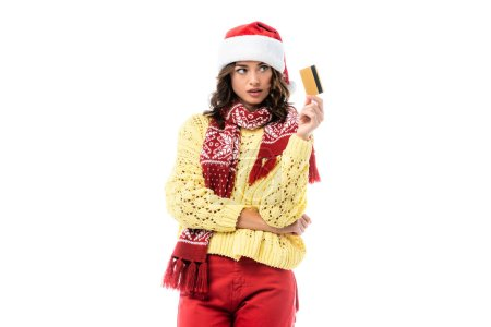 Photo for Young woman in santa hat and scarf looking at credit card isolated on white - Royalty Free Image
