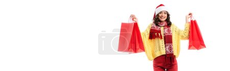 Photo for Panoramic crop of pleased young woman in santa hat and scarf with ornament holding red shopping bags isolated on white - Royalty Free Image