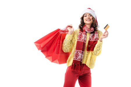 Photo for Joyful woman in santa hat and scarf with ornament holding shopping bags and credit card isolated on white - Royalty Free Image