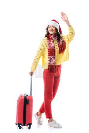 jeune femme en santa chapeau et écharpe avec ornement debout avec sac de voyage et main agitant isolé sur blanc