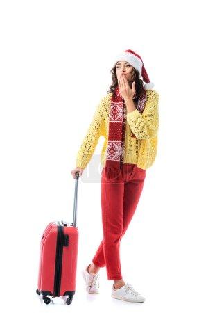 Photo pour Jeune femme en santa chapeau et écharpe avec ornement couvrant la bouche et debout avec sac de voyage isolé sur blanc - image libre de droit