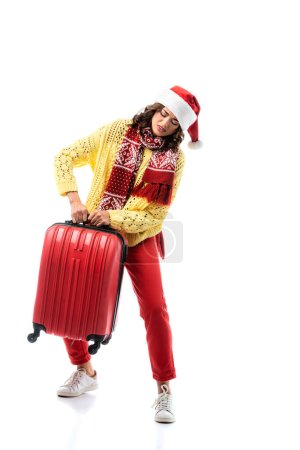 young woman in santa hat and scarf with ornament carrying heavy travel bag isolated on white
