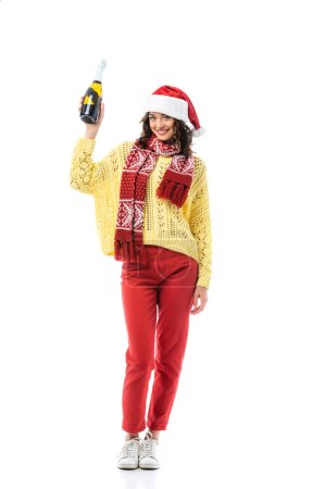 Photo for Happy young woman in santa hat and scarf with ornament holding bottle of champagne isolated on white - Royalty Free Image