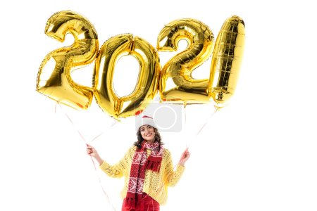 Photo for Joyful young woman in santa hat and scarf holding balloons with 2021 numbers isolated on white - Royalty Free Image