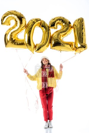 Photo for Pleased woman in santa hat and scarf holding balloons with 2021 numbers isolated on white - Royalty Free Image