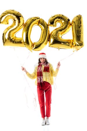 Photo for Young woman in santa hat and scarf holding balloons with numbers isolated on white - Royalty Free Image
