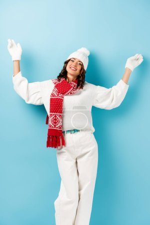 Photo for Joyful woman in winter outfit, warm scarf, gloves and hat standing with outstretched hands on blue - Royalty Free Image