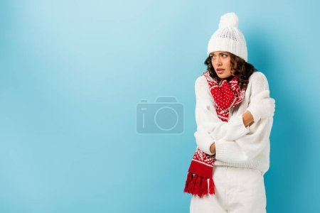 Photo for Freezing young woman in winter outfit embracing herself on blue - Royalty Free Image
