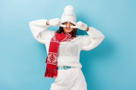 Photo for Young woman in white winter outfit showing peace sign on blue - Royalty Free Image