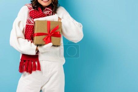 Photo pour Vue recadrée de la femme joyeuse en tenue d'hiver tenant enveloppé présent sur bleu - image libre de droit