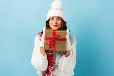 Photo pour Femme joyeuse en tenue d'hiver tenant présent enveloppé et regardant la caméra sur bleu - image libre de droit