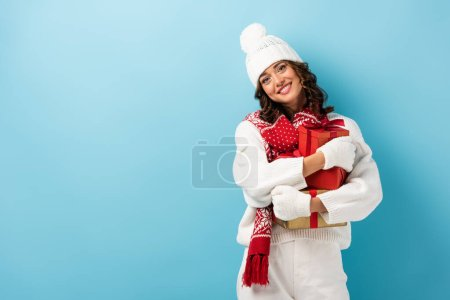 young pleased woman in white winter outfit holding presents on blue