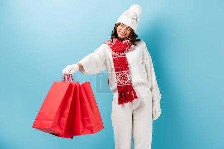 Photo pour Heureuse jeune femme en tenue d'hiver tenant des sacs à provisions rouges et regardant loin sur bleu - image libre de droit