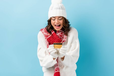 Photo for Excited young woman in winter outfit holding credit card on blue - Royalty Free Image