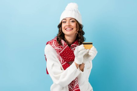 happy woman in winter outfit holding credit card on blue