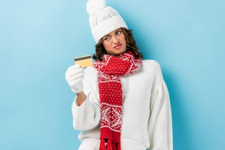 displeased young woman in white winter outfit holding credit card on blue