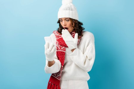 shocked woman in white winter outfit looking at mobile phone on blue