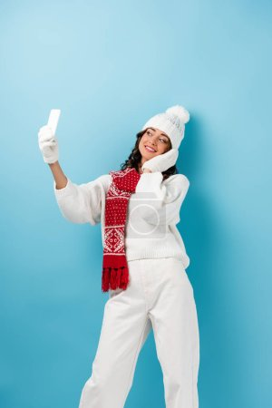 Photo for Young pleased woman in white winter outfit taking selfie on blue - Royalty Free Image