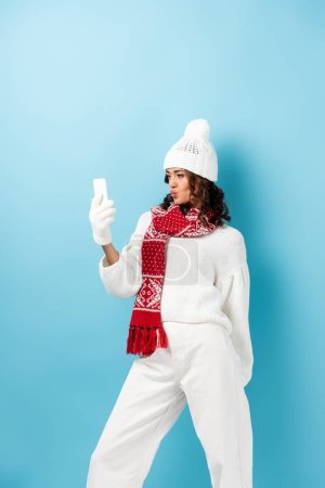 Photo for Young woman with duck face, in white winter outfit taking selfie on blue - Royalty Free Image