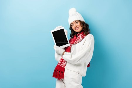 joyful young woman in winter outfit holding digital tablet with blank screen on blue