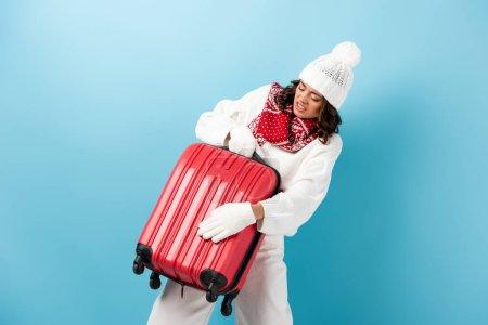 Photo pour Jeune femme en colère en tenue d'hiver portant une valise rouge sur bleu - image libre de droit
