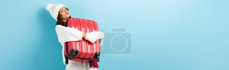 Photo for Panoramic shot of young woman in winter outfit carrying heavy suitcase on blue - Royalty Free Image