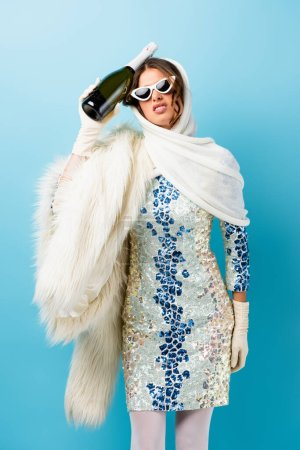 displeased woman in sunglasses holding bottle of champagne on blue