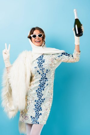 stylish woman in sunglasses smiling while holding bottle of champagne and showing peace sign on blue