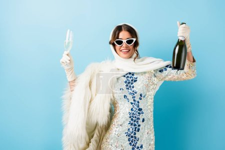 Photo for Pleased woman in sunglasses smiling while holding bottle of champagne and glass on blue - Royalty Free Image