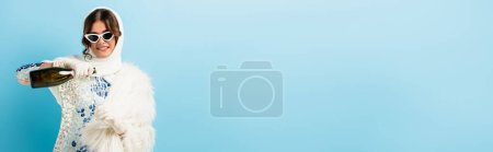 Photo for Panoramic crop of pleased woman in sunglasses holding bottle and pouring champagne in glass on blue - Royalty Free Image