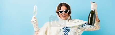 Photo for Horizontal image of joyful woman in sunglasses holding bottle of champagne and glass on blue - Royalty Free Image