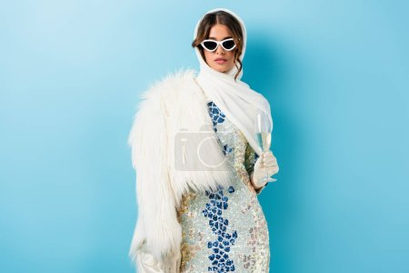 Photo for Stylish woman in sunglasses holding glass of champagne on blue - Royalty Free Image