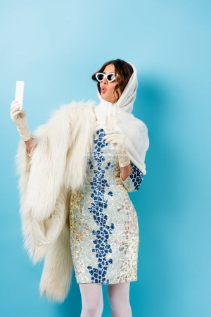 Photo for Stylish woman in sunglasses holding glass of champagne and taking selfie on blue - Royalty Free Image