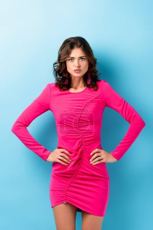 Photo for Displeased young woman in pink dress standing with hands on hips on blue - Royalty Free Image