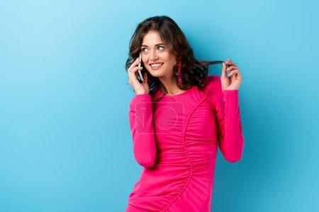 joyful woman talking on smartphone and touching hair on blue