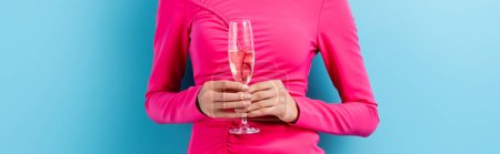 Photo for Panoramic crop of young woman holding glass of champagne on blue - Royalty Free Image