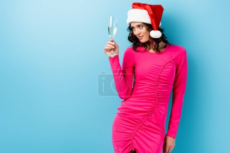 young brunette woman in santa hat looking at glass of champagne on blue