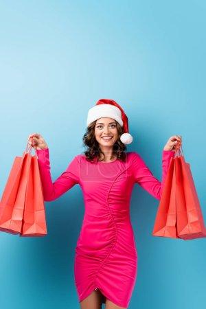 Photo pour Femme joyeuse en robe rose et chapeau santa tenant des sacs à provisions sur bleu - image libre de droit