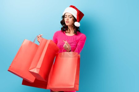 Photo for Young brunette woman in santa hat looking at shopping bags on blue - Royalty Free Image