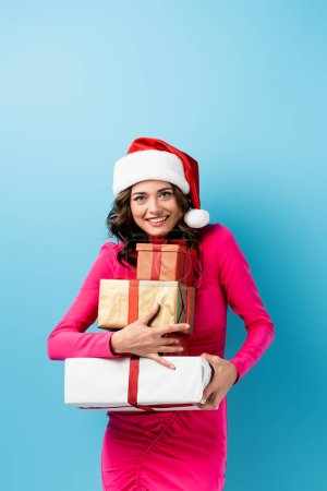 Photo pour Femme joyeuse en santa chapeau et robe tenant des cadeaux enveloppés sur bleu - image libre de droit