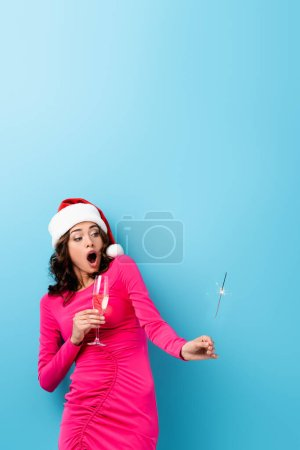 Photo for Shocked woman in santa hat holding sparkler and glass of champagne on blue - Royalty Free Image