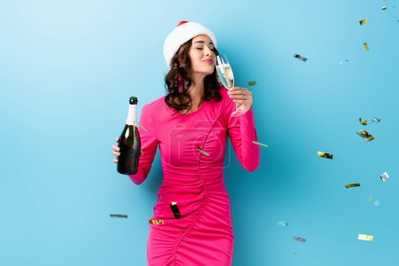 Photo pour Young woman in santa hat holding bottle and drinking champagne near confetti on blue - image libre de droit