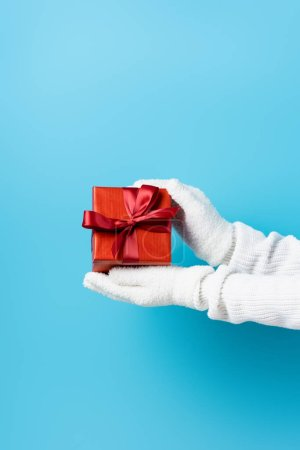 Photo for Partial view of young woman in gloves holding gift box on blue - Royalty Free Image