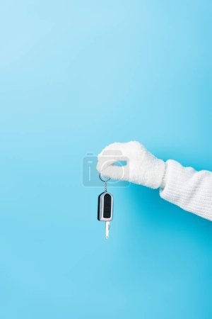 cropped view of woman in white glove holding key on blue