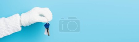 Photo for Panoramic crop of woman in white glove holding key on blue - Royalty Free Image