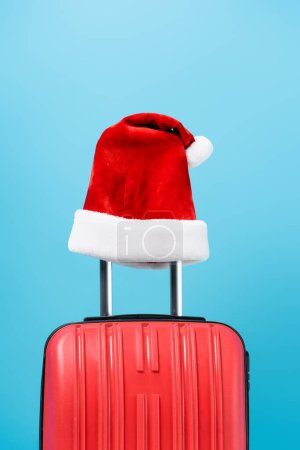 Photo for Red santa hat on modern travel bag isolated on blue - Royalty Free Image